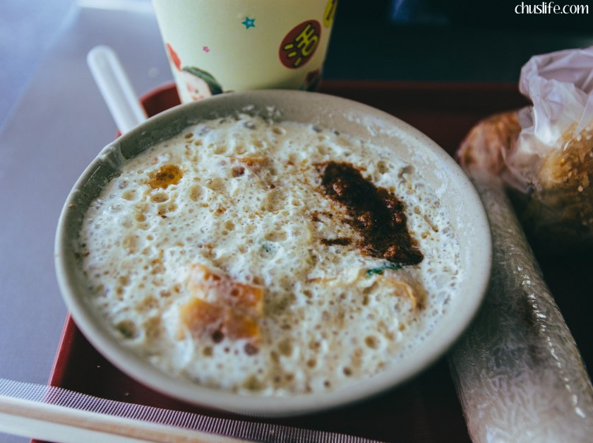 Hot, savory soy milk. It's curdled with vinegar, then topped with stuff like green onions, fried breadstick pieces, etc.